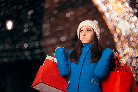 a woman looks slightly overwhelmed while doing her holiday shopping